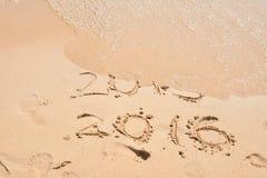 波浪报道数字2015年 概念新年度 在海滩沙子的题字2015年和2016年 新年快乐2016年 库存图片