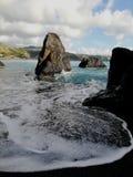 波浪拥抱岩石 免版税库存照片