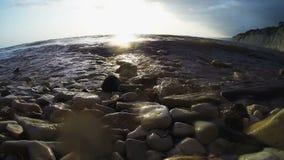 波浪滚动在与太阳强光的日落在岩石的岩石海滨 影视素材