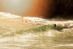 波浪的冲浪者在日落 免版税库存图片