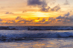 波浪的现出轮廓的在明亮的色的天空的冲浪者和云彩在日落期间 热带海滩的夜间 库存照片