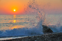 波浪碰撞的岩石创造水漩涡日落 免版税库存照片