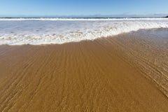 波浪舔一个金黄沙子海滩 库存照片