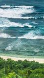 波浪落下并且供以人员调查在Nunggalan海滩的元素 Uluwatu,巴厘岛,印度尼西亚 图库摄影