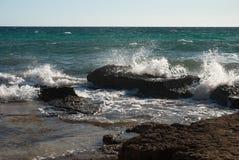 波浪被击中的黑岩石 免版税库存照片