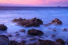 波浪长的曝光在多岩石的海滩的有紫色日落背景 库存图片