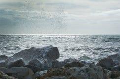 波浪飞溅在岩石上 图库摄影