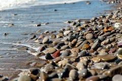 波浪洗涤的海小卵石 库存图片