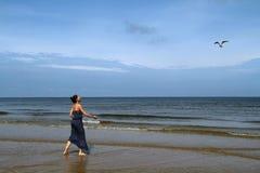 波罗的海、妇女走沿海滩的和哺养的白顾 库存照片