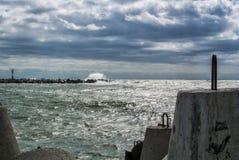 波罗的海的堤防城市的Baltiysk多云夏日、一个看法对痣,波浪和大石块在码头 免版税库存照片