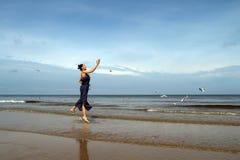 波罗的海,夏天礼服哺养的白色鸥的妇女在bea 免版税库存图片