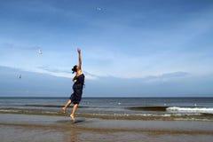 波罗的海,夏天礼服跳跃的和哺养的白色g的妇女 库存照片