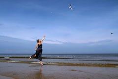波罗的海,杨妇女夏天礼服跳跃的和哺养的wh的 图库摄影
