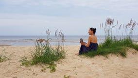 波罗的海,象草的沙丘的妇女与一个软的玩具在手上 免版税库存照片