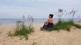 波罗的海,象草的沙丘的妇女与一个软的玩具 免版税库存图片