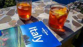 波西塔诺,意大利,2017年4月:游遍意大利在旅行指南的帮助下和享受著名意大利语Aperol喷 免版税图库摄影