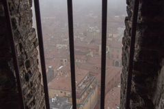 波隆纳典型的红色屋顶在一有雾的天 从Asinelli塔一个狭窄的窗口的看法  伊米莉亚罗马甘,意大利 免版税库存图片
