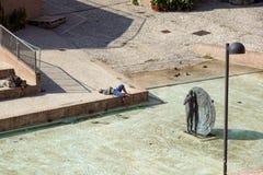 波隆纳,意大利- 2018年4月15日: 一个未认出的人通过采取太阳放松在现代城市广场 afr 库存图片