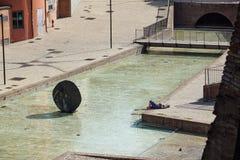 波隆纳,意大利- 2018年4月15日: 一个未认出的人通过采取太阳放松在现代城市广场 afr 库存照片