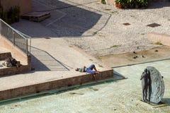 波隆纳,意大利- 2018年4月15日: 一个未认出的人通过采取太阳放松在现代城市广场 afr 免版税图库摄影