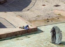 波隆纳,意大利- 2018年4月15日: 一个未认出的人通过采取太阳放松在现代城市广场 afr 免版税库存图片
