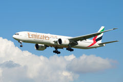 波音777-300 (A6-EGU)阿联酋国际航空从多云天空涌现 库存图片