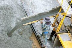 从水泥卡车,人工作者的建筑工人倾吐的混凝土 免版税库存照片