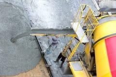 从水泥卡车,人工作者的建筑工人倾吐的混凝土 免版税图库摄影