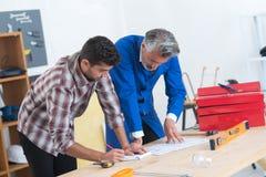 泥工和工程师测量的计划 免版税库存图片