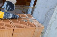 泥工操练与机械钻的一个孔 免版税库存照片