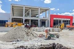 水泥搅拌车机器和独轮车在建筑工地 库存图片