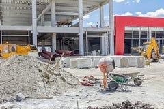 水泥搅拌车机器和独轮车在建筑工地 免版税库存图片