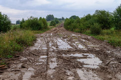泥泞的土路在多小山乡下 免版税库存图片