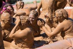 泥泞的妇女飞溅在肮脏的女孩泥奔跑 库存图片