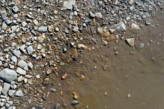 泥泞的水坑水和石头 免版税库存照片