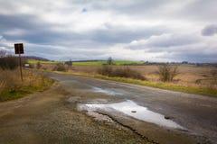 泥泞的街道在有水坑的一个村庄 图库摄影