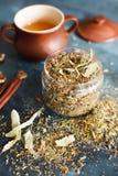 泥罐用蜂蜜、肉桂条、坚果和草本汇集 免版税库存照片