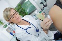 注射从玻璃瓿的女性医生医疗解毒剂注射器 免版税库存照片