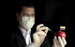 注射化学制品的年轻商人入与哥伦比亚的旗子的一个苹果在黑背景 免版税库存照片