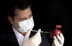 注射化学制品的年轻商人入与安哥拉旗子的一个苹果 图库摄影