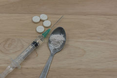 注射器和药物和匙子烹调了在木背景的海洛因 在工作室 库存照片