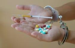 注射器和药物在手中和手铐 免版税库存照片
