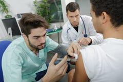 注射患者的年轻内科医生医生在监视外 库存照片