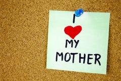 注意充满I爱我的母亲、笔记充满I爱我的妈妈和红色心脏在黄柏板背景 库存照片