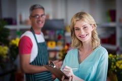 注意关于剪贴板的微笑的女性卖花人在花店 免版税库存图片