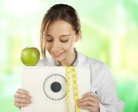 注意和拿着重量缩放比例和绿色苹果的营养学家 免版税库存照片