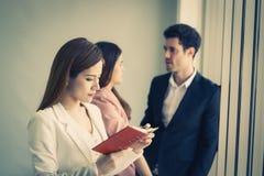 注意在两个朋友办公室工作者前面的商人在背景中 对妇女信心概念 免版税库存照片