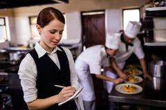 注意在笔记薄的女性女服务员命令在厨房里 图库摄影
