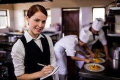 注意在笔记薄的女性女服务员命令在厨房里 库存图片