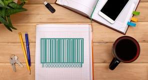 注意在笔记薄的条形码产品在书桌上 免版税库存照片